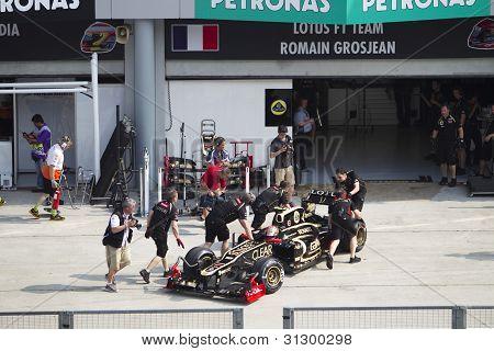 Romain Grosjean pushed back to his pit garage
