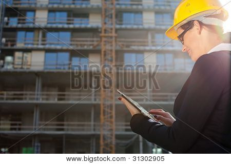 Young Female Architect/construction Engineer Using Tablet Computer At A Construction Site
