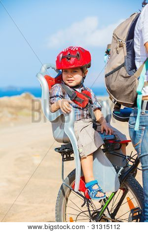 child sitting by bicycle in crash helmet