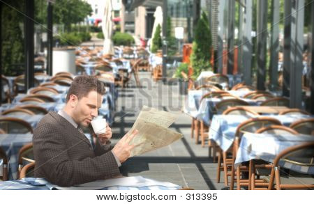 Resting Businessman Drinking Coffee And Reading Newspaper In The Restaurant