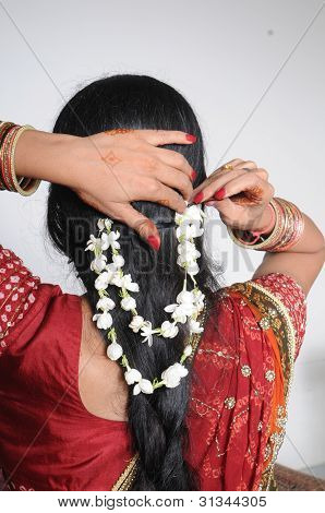 Indian girl decorating her long hairs with flowers.