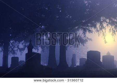 Cemetery headstones on a foggy morning