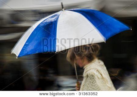 Woman under blue striped umbrella