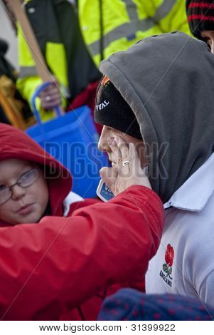 A Young Barral Roller Gets Some Vasaline On Their Face At The Start Of The 2011 Tar Barrels Of Otter