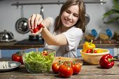 Young Cheerful Girl Prepares A Vegetarian Salad In The Kitchen, She Adds Sliced Ingredients To The P poster