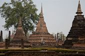 Female Tourist With A Bright Umbrella Among Pagodas In Famous Sukhothai Historical Park, A Unesco Wo poster