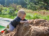 Little Toddler Boy Exploring A Pile Of Sand. The Child Touches The Sand, Crawls Through The Sand, Sq poster