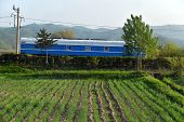 Old Railway Car On Railway Tracks In Countryside. North Korea. Dprk. Agricultural Fields On Foregrou poster