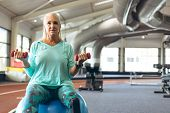 Front view of disabled active senior woman with leg amputee exercising with dumbbell while sitting o poster