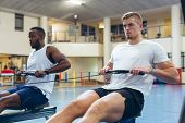 Front view of young fit diverse male athletes exercising with rowing machine in fitness studio. Brig poster