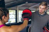 Close-up of fit Caucasian male trainer giving boxing training to pretty Caucasian female athletic. B poster