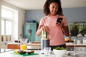 Woman Using Fitness Tracker To Count Calories For Post Workout Juice Drink He Is Making poster