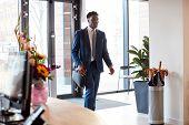 Businessman Arriving For Work At Office Walking Through Door poster