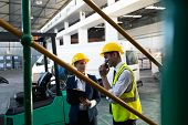 Front view of Caucasian female manager and Caucasian male supervisor working together in warehouse.  poster
