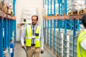 Front view of handsome mature Caucasian male supervisor walking in warehouse. This is a freight tran poster