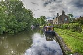 Narrowboat Moored Up In English Rural Countryside Scenery On British Waterway Canal During Overcast  poster