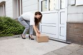 Smiling Young Woman Peeking Up The Delivered Parcel At The Door Entrance poster