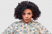 Portrait Of Serious Young African American Woman Wearing Floral Shirt, Looking To The Camera, Has Fr poster