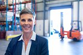 Portrait close-up of beautiful mature Caucasian female manager looking at camera in warehouse. This  poster