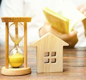 Wooden House And Clock. Businessman Counting Money. Payment Of Deposit Or Advance Payment For Rentin poster