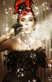 picture of birthday party  - Beautiful party girl in haute couture and a fascinator hat blowing a myriad of iridescent bubbles during a birthday celebration - JPG