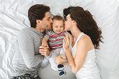 Enjoying Parenthood. Happy Caucasian Couple Kissing Sweet Cheeks Of Their Adorable Baby Son, Lying T poster
