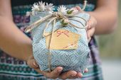Hands Holding Gift Box With Flowers. Gift Present. Close Up Of Hands Holding Gift Box With Natural T poster
