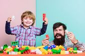 Dad And Child Build Plastic Blocks. Happy Family. Child Development And Upbringing. Importance Of Pl poster
