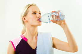 stock photo of bottle water  - Portrait of young pretty girl drinking water from bottle with towel on her shoulder - JPG