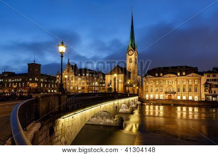 Illuminated Fraumunster Church And River Limmat In Zurich, Switzerland