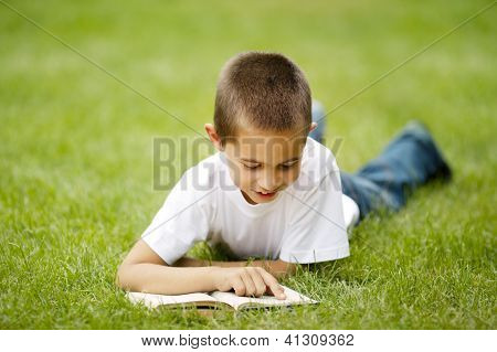 little happy boy reads book lying on grass