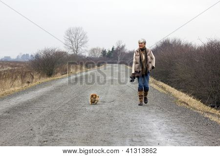 Senior woman walking her dog on an overcast winter day.