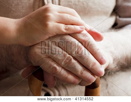 Senior man and little girl hands