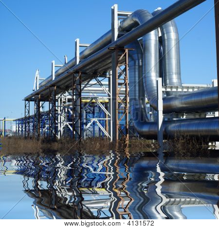 Industrial Pipelines On Pipe-Bridge Against Blue Sky  With Reflection