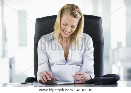 Businesswoman In Office Looking At Personal Organizer Smiling