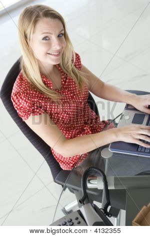 Businesswoman Sitting In Office Typing On Laptop Smiling