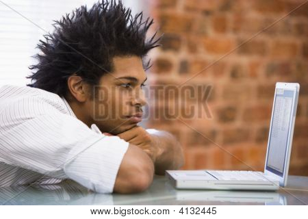 Businessman Sitting In Office With Laptop