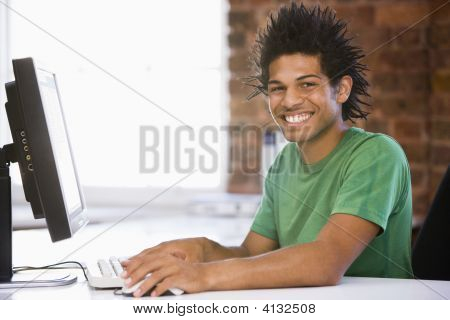 Businessman In Office Typing On Computer Smiling