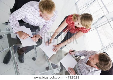 Three Businesspeople In Boardroom With Paperwork