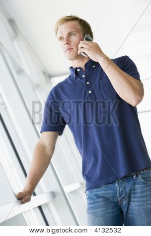Man Standing In Corridor Smiling Using Cellular Phone