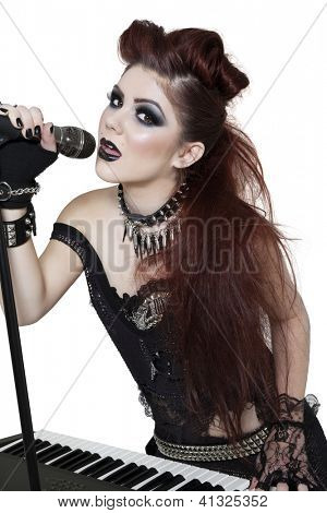 Portrait of beautiful punk woman playing piano while singing with microphone over white background