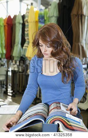 Bella joven mirando muestras de textiles en tienda