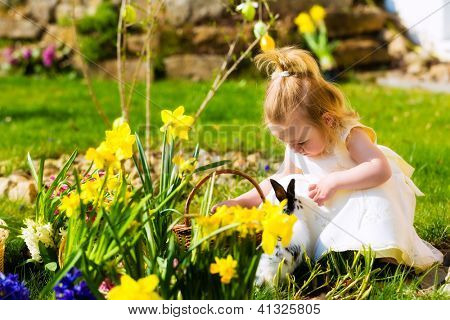 Little Girl on an Easter Egg hunt on a meadow in spring, she has found an Easter egg, the easter bunny comes to meet her