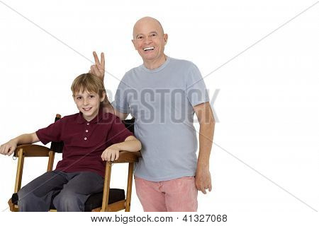 Senior man gesturing peace sign while preteen boy sitting on director's chair over white background