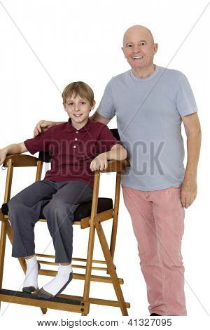Portrait of senior man with preteen boy sitting on director's chair over white background