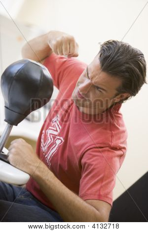 Man Indoors Using Small Punching Bag