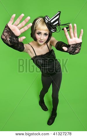 Young woman posing with fingerless gloves and headdress over green background
