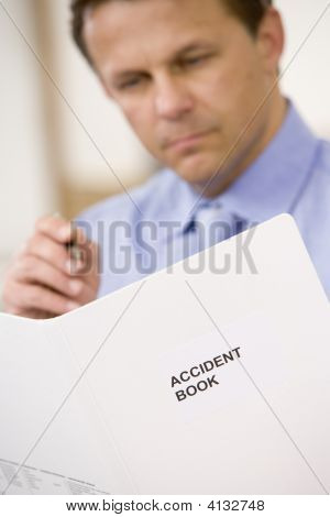 Businessman Indoors Looking At Accident Book
