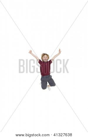 Elementary boy jumping in air with arms raised over white background