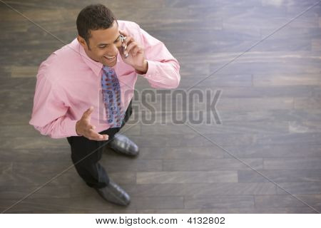 Businessman Standing Indoors Using Cellular Phone Smiling